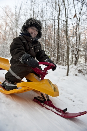 to steer a sledge: Young boy having fun going dowbhill on a snow sledge