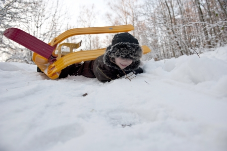 Young boy doing an overturn with a snow sledge photo