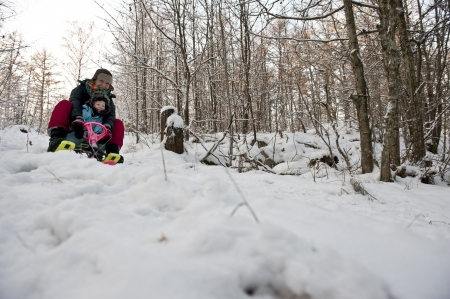 to steer a sledge: Mother and child going downhill on a snow sledge