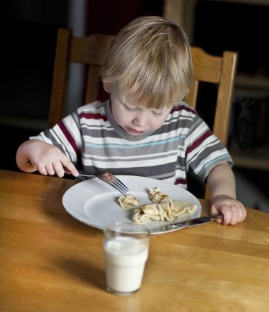 Young boy eating pancake and drinking milk