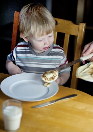 Young caucasian boy getting served some more pancakes Stock Photo