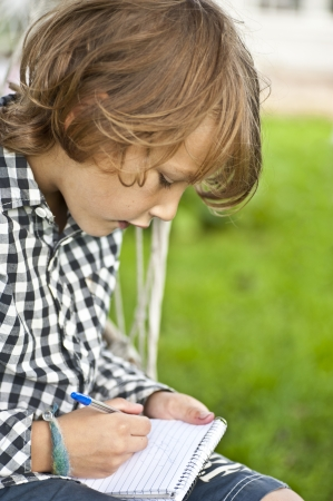 oudoors: Young boy sitting oudoors drawing in a notepad  Stock Photo