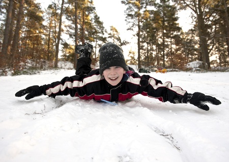 Young boy gliding on his belly in the snow