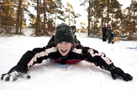 Young boy gliding on his belly in the snow Stock Photo - 17414354