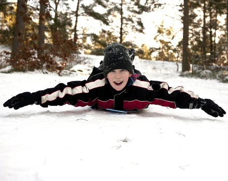 Young boy gliding on his belly in the snow Stock Photo - 17414349