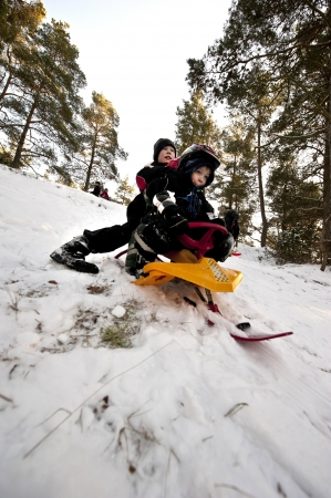 Two young boys going downhill on a snow sledge photo