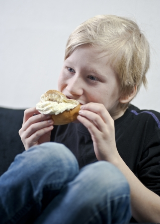 Young boy eating a traditional swedish cream bun Stock Photo - 17419602