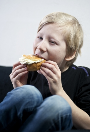 Young boy eating a cream bun Stock Photo - 17419595