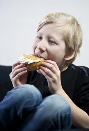 Young boy eating a cream bun