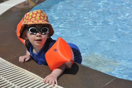 Young boy at poolside in swimsuit and swimming glasses
