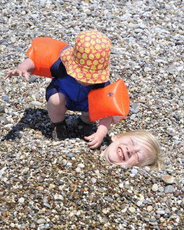 A young boy covering his elder brother with pebbles on the beach  photo