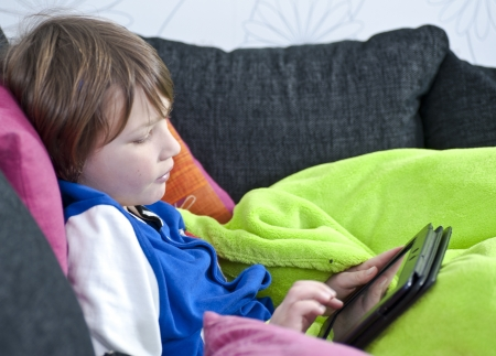 Young boy in sofa playing with a tablet