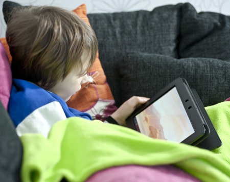Young boy in sofa playing a game on a tablet
