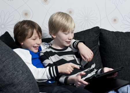 Two young kids in a sofa having fun together with a tablet