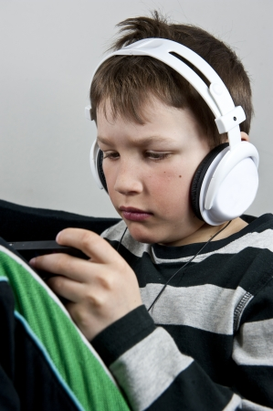 Young boy listening to music in earphones wile playing or texting on a cellphone Stock Photo
