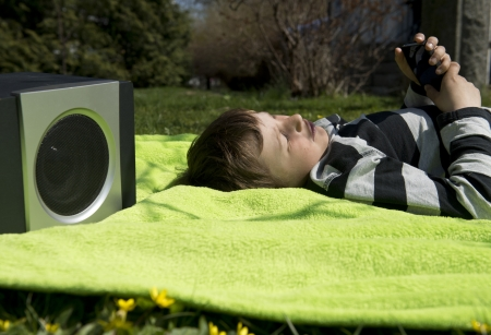 Young boy laying on a blanket in the grass listening to music streaming from his smartphone to a wireless and portable speaker