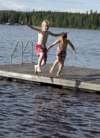 Two happy boys jumping in a lake from a bridge