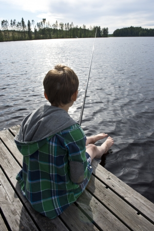 Young boy on bridge angling in a lake  Stock Photo