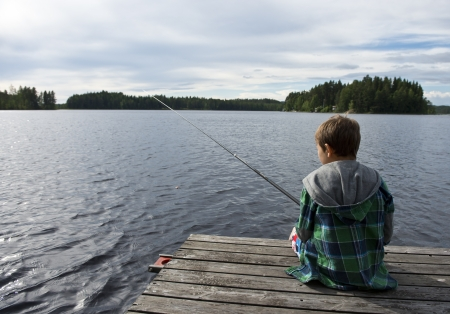Young boy on bridge angling in a lake