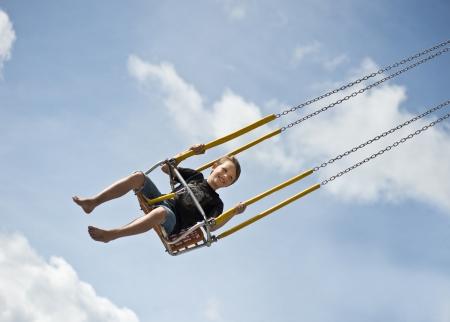 Jonge jongen rijdt op een swingende carrousel