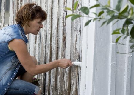 devanture: Femme peignant la fa�ade d'une vieille maison