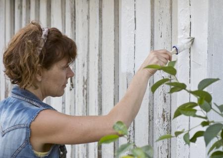 devanture: Femme peignant la fa�ade d'une maison ancienne Banque d'images