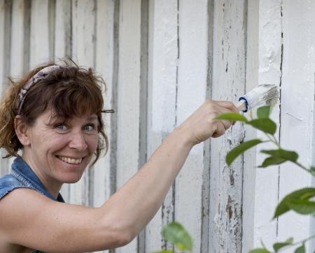 devanture: Bonne femme peignant la fa�ade d'une maison ancienne