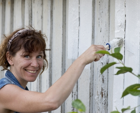 Happy woman painting the frontage of an old house  photo