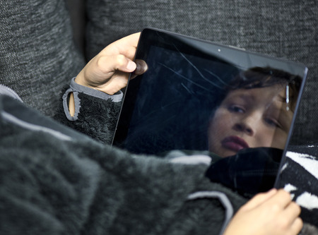 Image of a sad boys face reflected in a broken tablet