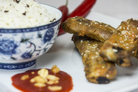 Hot and spicy spareribs served with rice and chili and peanuts