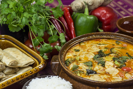Bowl of panang curry stew surrounded with vegetables and spices