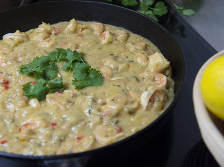 Cooking prawns with herbs in a frying pan