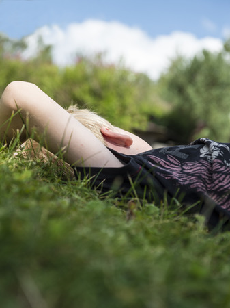 Young boy dreaming away while relaxing in the grass