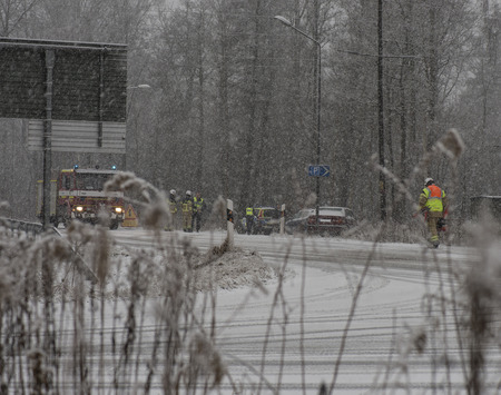Rescuepersonal at a car crash at wintertime