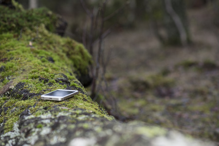 Cellphone lost or forgotten on a resting spot in nature