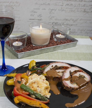 Grilled pork filled with herbs and wrapped in bacon served with potatoes au gratin and grilled vegetables