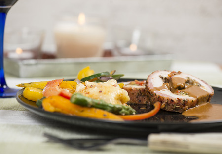 Stuffed and grilled pork fillet served with potatoes au gratin and grilled vegetables