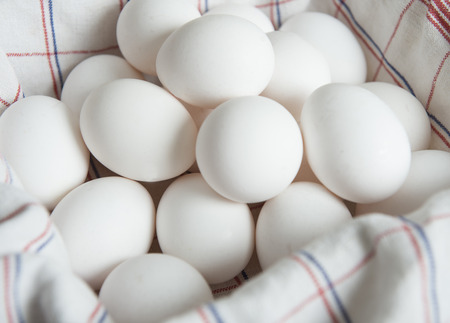 White egges in a basket protected by a kitchen cloth Imagens