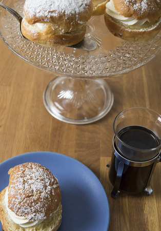 Table set with hot black coffe and creamy almond buns