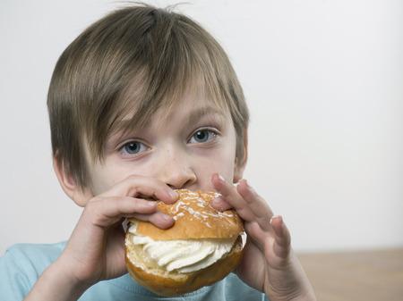 Young boy eating a tasty cream bun Imagens