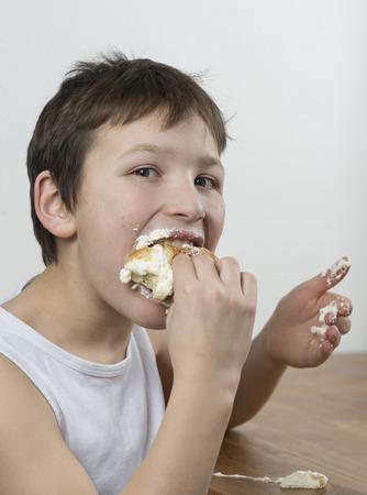 munching: Young boy munching on a cream bun