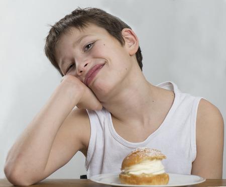 Young boy waiting for his cream bun