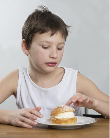 Young boy with a tasty cream bun Stock Photo