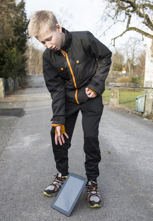 blasted: Young boy dropping his tablet on a walk outdoors Stock Photo