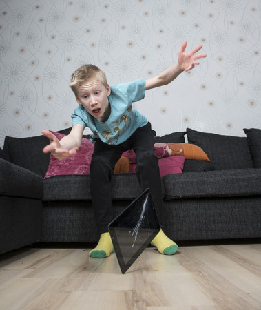 blasted: Young boy dropping his tablet on the floor Stock Photo
