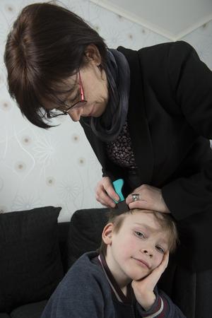 piojos: Madre comprobar cabeza del ni�o para los piojos con un peine