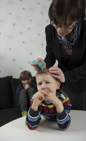 piojos: Madre comprobar cabeza del niño para los piojos con un peine