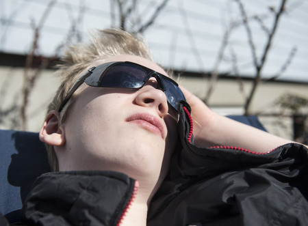 Male teenager enjoying the first warming sunbeams at springtime