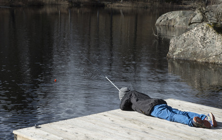 Young boy looking for fish while fishing photo