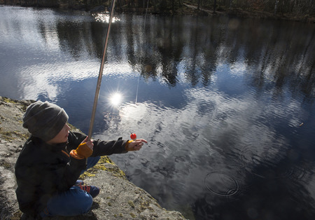 Young fisher checking his bait on springtimes first fishing trip